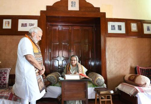 The Prime Minister of Bangladesh, Ms. Sheikh Hasina signing the visitors' book at Santi Niketan, in West Bengal on May 25, 2018. The Prime Minister, Shri Narendra Modi is also seen.